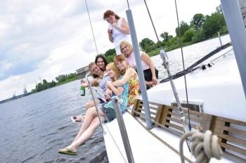 Отдых на яхте - девушки на носу яхты с шампанским